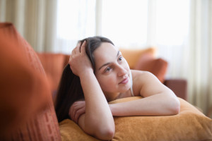 Thoughtful Woman Lying On Sofa