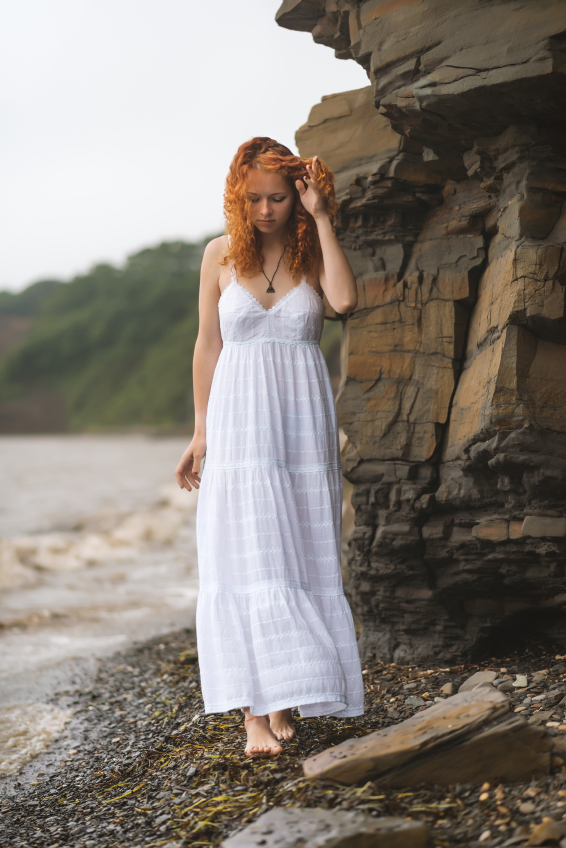 Beautiful redhead woman goes along the coast.